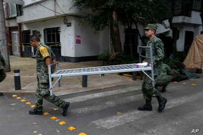 Soldiers carry a cot as they break camp from earthquake-torn Condesa neighborhood of Mexico City, Oct. 3, 2017.