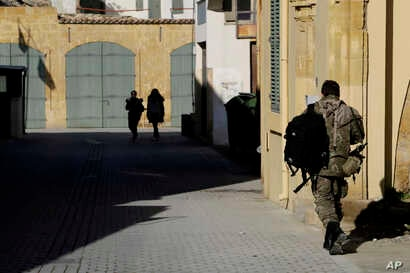 A Greek Cypriot soldier (R) walks towards a military guard post across the UN buffer zone that divides the Greek and Turkish Cypriots controlled areas, in the divided capital Nicosia, Mediterranean island of Cyprus, Jan. 12, 2017.