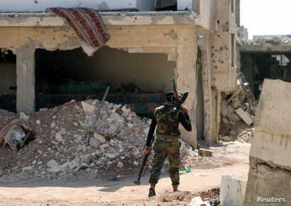 A Free Syrian Army fighter carries weapons as he walks past damaged buildings in a rebel-held part of the southern city of Deraa, Syria July 9, 2017.