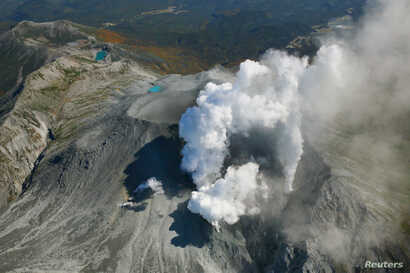 Volcanic smoke rises from Mount Ontake, which straddles Nagano and Gifu prefectures, central Japan, September 29, 2014, in this photo taken and released by Kyodo. More than 500 rescuers in Japan resumed searching on Monday for victims of the volcano ...