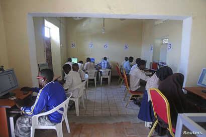 FILE - People use computers at an internet cafe in the Hodan area of Mogadishu, Oct. 9, 2013.