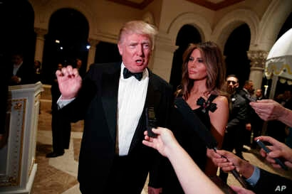President-elect Donald Trump talks to reporters during a New Year's Eve party at Mar-a-Lago, Dec. 31, 2016, in Palm Beach, Fla. His wife, Melania Trump, looks on.