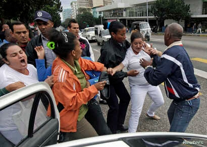 Cuban security personnel detain members of the Ladies in White group during a protest on International Human Rights Day, in Havana, Dec. 10, 2014.
