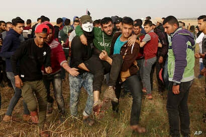 Palestinian protesters evacuate a wounded youth during clashes with Israeli troops along Gaza's border with Israel, east of Khan Younis, Gaza Strip, April 5, 2018. An Israeli airstrike in northern Gaza early Thursday killed a Palestinian, while a sec...