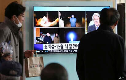 People watch a TV screen showing a local news program reporting about North Korea's missile launch, at the Seoul Railway Station in Seoul, South Korea, Nov. 30, 2017.