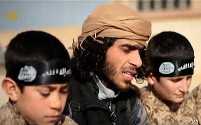 А YouTube screen grab from an Islamic State propaganda video shows an IS recruiter with two child soldiers. Children as young as eight years old are reportedly being trained to serve in roles ranging from spies, to front line soldiers, to suicide bo...