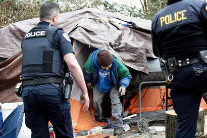 Leroy Henry, center, steps out of his tent in the woods to talk with police officer Kevin Davis, left, and Sgt. Mike Braley in Everett, Washington, Feb. 16, 2017.