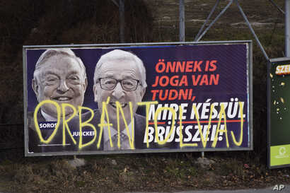"""A billboard from a campaign of the Hungarian government showing EU Commission President Jean-Claude Juncker and Hungarian-American financier George Soros with the caption """"You, too, have a right to know what Brussels is preparing to do"""" is displayed ..."""