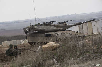 An Israeli tank and soldiers take positions on the Israel-Gaza border, Nov. 16, 2018.