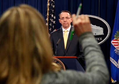 FILE - A reporter raises her hands to ask a question of Deputy Attorney General Rod Rosenstein, after he announced the office of special counsel Robert Mueller says a grand jury has charged 13 Russian nationals and several Russian entities, Feb. 16, ...