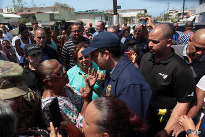 Puerto Rico's Governor Ricardo Rossello (center) talks to a woman during a distribution of relief items, after the area was hit by Hurricane Maria in San Juan, Puerto Rico Sept. 24, 2017.