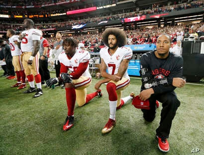FILE -  San Francisco 49ers quarterback Colin Kaepernick (7) and outside linebacker Eli Harold (58) kneel during the playing of the national anthem before an NFL football game against the Atlanta Falcons in Atlanta.