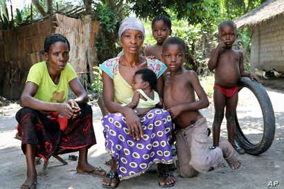 A family sits outside in a neighborhood where three people died of Ebola last month, in Mbandaka, Congo, June 1, 2018. For the first time since the Ebola virus was identified more than 40 years ago, a vaccine has been dispatched to front line health ...