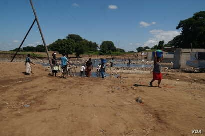 Residents of the heaviest-hit southern areas draw water from small rivers created by the floods. (L. Mesina for VOA)