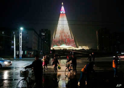 People cross a street as pyramid-shaped Ryugyong Hotel is seen in the background in Pyongyang, North Korea, Dec. 18, 2018. Transformed into the backdrop for a gargantuan propaganda display, Pyongyang's yet-to-be-completed 105-story Ryugyong Hotel is ...