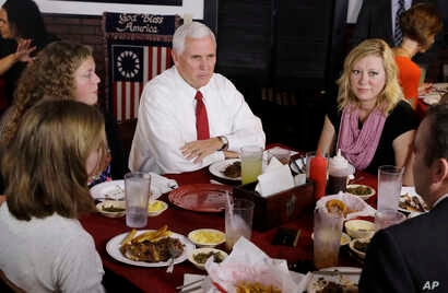 Vice President Mike Pence talks with the McCurry family during a visit to The Pittt Barbecue & Grill, in Anderson, Indiana, Sept. 22, 2017.