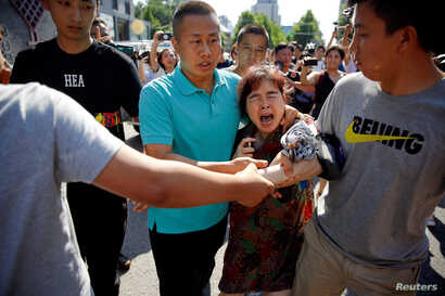 A woman is detained by security personnel outside the U.S. embassy in Beijing, China, July 26, 2018.