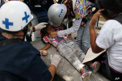 Volunteer paramedics give assistance to child that was affected by tear gas when she caught with her mother between authorities and anti-government demonstrators in Caracas, Venezuela, June 14, 2017.