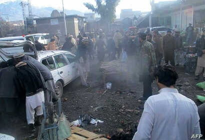 Pakistani security officals and local residents are seen gathered at the site of a bomb explosion at a market in Parachinar city, the capital of Kurram tribal district on the Afghan border on Jan. 21, 2017.
