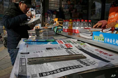 FILE - A man arranges magazines near newspapers with the headlines of China outcry against U.S. on the detention of Huawei's chief financial officer, Meng Wanzhou, at a news stand in Beijing.