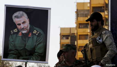 FILE - Members of the mainly Shi'ite Hashid Shaabi militia hold a portrait of Quds Force Commander Qassem Suleimani during a demonstration to show support for Yemen's Shi'ite Houthis and in protest of an air campaign in Yemen by a Saudi-led coalition...