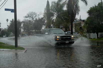 A truck makes it way through flooded streets of Panorama City section of the San Fernando Valley in Los Angeles, Feb. 2, 2019. Flash flood warnings were issued for vast swaths of Southern California and authorities urged motorists not to drive throug...