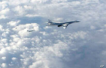 In this image made available by the Royal Air Force, Jan. 15, 2018, two Russian Blackjack Tupolev Tu-160 long-range bombers are followed by an RAF Typhoon aircraft, left, scrambled from RAF Lossiemouth, Scotland.