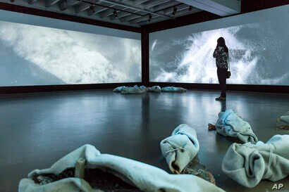 """A visitor views an artwork titled End of Dreams by Danish artist Nikolaj Bendix Skyum Larsen for an exhibition """"Islam, It's Also Our History"""" at the Espace Vanderborght in Brussels, Sept. 19, 2017."""