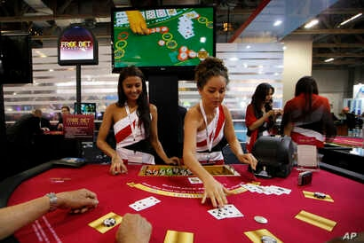 FILE - Attendants conduct play with the visitors over a Black Jack gaming table during the Global Gaming Expo Asia in Macau.
