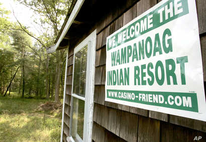 FILE — A poster declaring support for bringing a casino to Middleborough, Mass., appears on the side of a small house on property adjacent to land belonging to the Mashpee Wampanoag tribe.