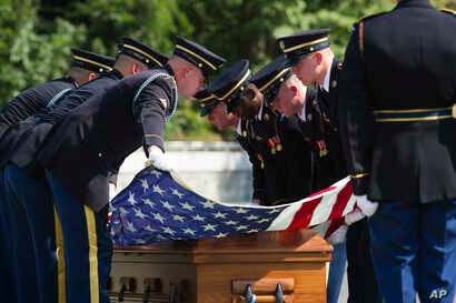 FILE - In this Sept. 6, 2018 photo, the 3rd Infantry Regiment stretches the American flag over the casket containing the remains of one of two unknown Civil War Union soldiers at Arlington National Cemetery in Arlington, Va.