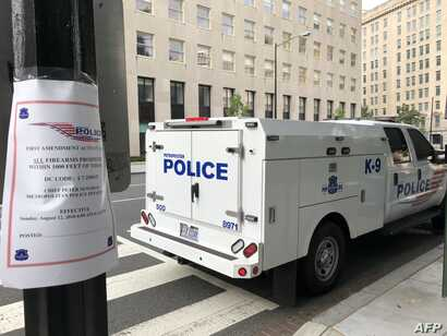 """A sign is posted on """"first ammendment activities"""" and the prohibition of firearms as police patrol a street two blocks from the White House on Aug. 12, 2018 in Washington, DC."""
