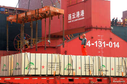 A worker gestures as a crane lifts goods onto a cargo ship, at a port in Lianyungang, Jiangsu province, China, May 31, 2018.