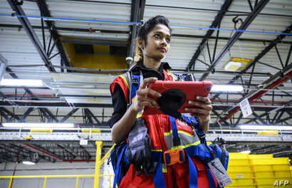 A woman uses a computer to control robots at the 855,000-square-foot Amazon fulfillment center in Staten Island, one of the five boroughs of New York City, Feb. 5, 2019.