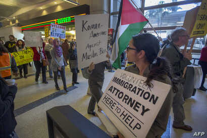 Demonstrators pass a volunteer immigration attorney as they march in support of a ruling by a federal judge in Seattle that grants a nationwide temporary restraining order against the presidential order to ban travel to the United States from seven ...