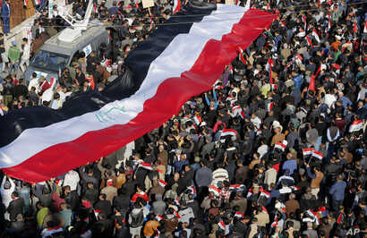 Followers of Iraq's influential Shiite cleric Muqtada al-Sadr chant slogans as they wave national flags during a demonstration against corruption in Baghdad, Iraq, Feb. 11, 2017.