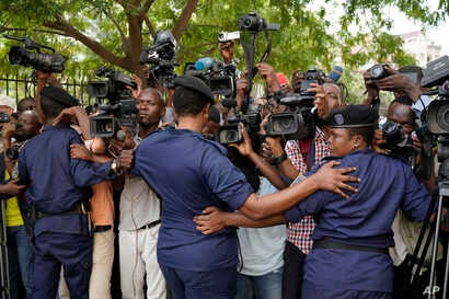Congolese police officers hold back members of the media as Congo opposition candidate Martin Fayulu leaves the constitution court in Kinshasa, Congo, Saturday Jan. 12, 2019.