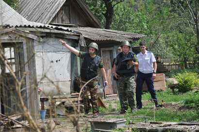 Members of a Russian investigative committee examine a house after shelling in Donetsk, Russia, July 13, 2014.