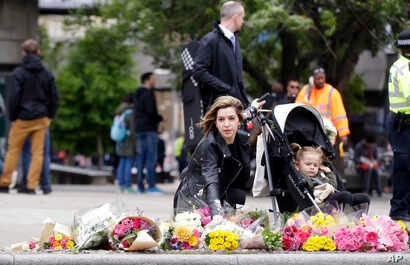 A woman lays a bouquet of flowers in the London Bridge area of London, June 5, 2017.