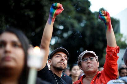 People attend a vigil in memory of victims one day after a mass shooting at the Pulse gay night club in Orlando, in Los Angeles, California, June 13, 2016.