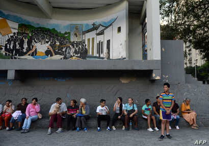 People wait in the streets after evacuating buildings in Caracas, Aug. 21, 2018, following a 7.3-magnitude earthquake that struck in Venezuelan northeastern state of Sucre according to the U.S. Geological Survey.