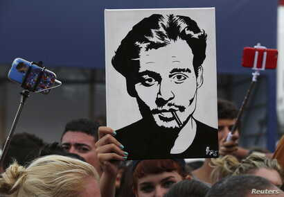 A girl (C) holds up a portrait of actor Johnny Depp in front of the entrance of the venue of the 72nd Venice Film Festival, northern Italy, Sept. 4, 2015.