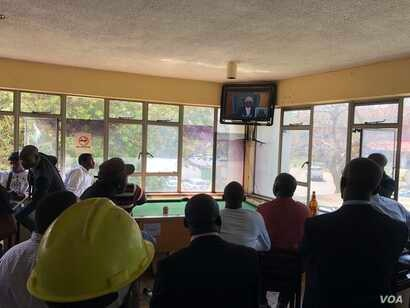 Zimbabweans are seen gathered at a bar in Harare, Aug. 22, 2018, where they are following proceedings on a presidential election challenge filed at the Constitutional Court by Zimbabwe's main opposition group. (C. Mavhunga/VOA)