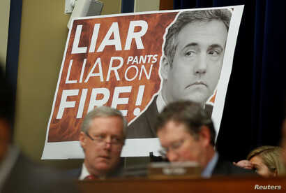 """A sign reading """"Liar Liar Pants on Fire!"""" is seen behind Rep. Mark Meadows (R-NC) and other Republican members of the committee during the testimony of former Trump personal attorney Michael Cohen at a House Committee on Oversight and Reform hearing ..."""