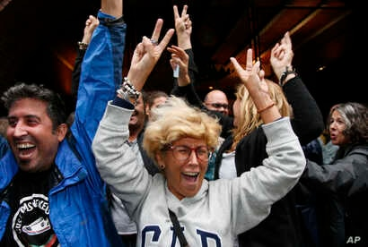 People cheer after voting at a school assigned to be a polling station by the Catalan government at the Gracia neighborhood in Barcelona, Spain, Oct. 1, 2017.