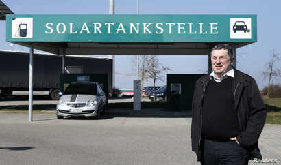 FILE - Juergen Silberzahn, mayor of Wolpertshausen, poses in front of a service station for electric cars powered by solar energy, in the village of Wolpertshausen near Schwaebisch Hall, Germany, March 18, 2016.