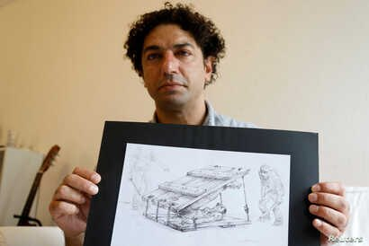 Exiled Syrian artist Najah al-Bukai poses with a ball-pen drawing that stems from the haunting memories of the torture Bukai says he went through and witnessed when imprisoned twice in Syrian government jails, in Yerres, near Paris, Sept. 13, 2018.