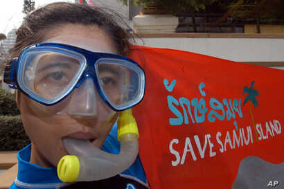 FILE - A Thai activist from Greenpeace holds a banner in protest of toxic pollution of Samui Island in front of the Tourism Authority of Thailand in Bangkok, March 8, 2005.