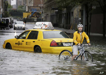 FILE - A bicyclist makes his way past a stranded taxi on a flooded New York City street as Tropical Storm Irene passes through the city,  Aug. 28, 2011. A June 2012 study in Nature Climate Change said that by the year 2100, scientists and computer mo...