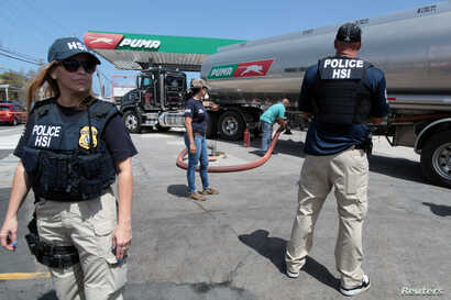 Federal agents provide security to a truck discharging gas at a gas station, after the island was hit by Hurricane Maria, in San Juan, Puerto Rico, Sept. 28, 2017.